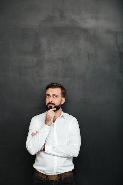 Retrato de hombre con barba morena en camisa blanca tocando su barbilla pensando o recordando sobre gris oscuro Foto gratis