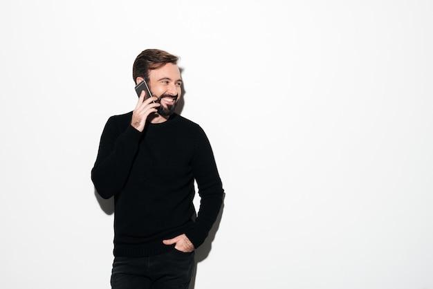 Retrato de un hombre barbudo alegre hablando por teléfono móvil Foto gratis