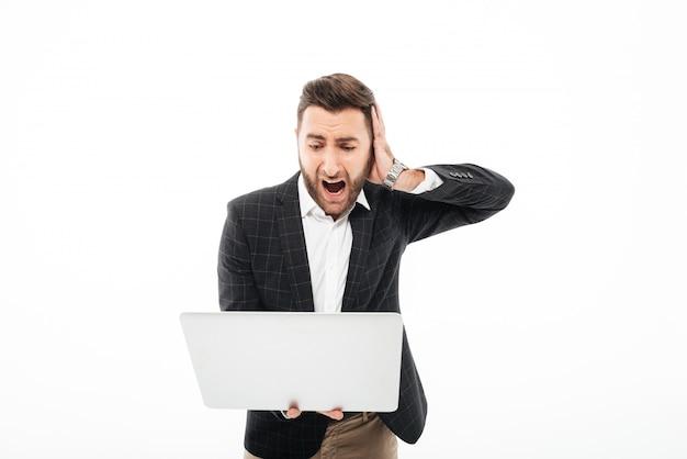 Retrato de un hombre barbudo enojado con ordenador portátil Foto gratis