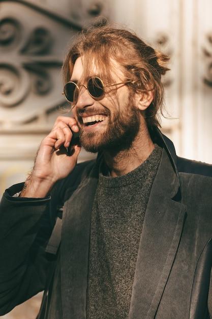 Retrato de un hombre barbudo feliz en gafas de sol Foto gratis