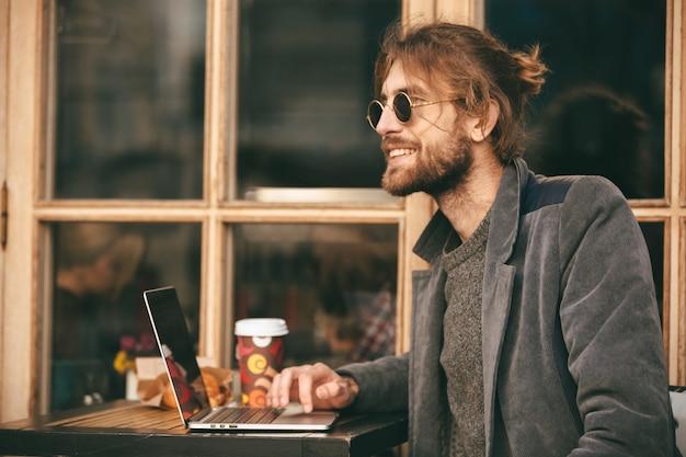 Retrato de un hombre barbudo sonriente en auriculares sentado al aire libre Foto gratis
