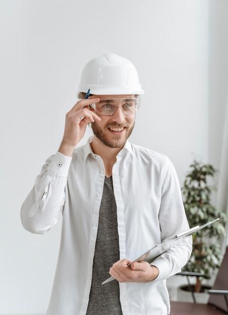 Retrato de hombre con casco en la oficina Foto gratis