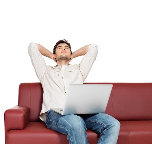 Retrato de hombre descansando con portátil se sienta en el diván, aislado en blanco. Foto gratis