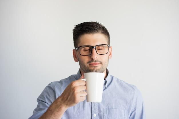 Retrato de hombre con gafas disfrutando de café con los ojos cerrados. Foto gratis