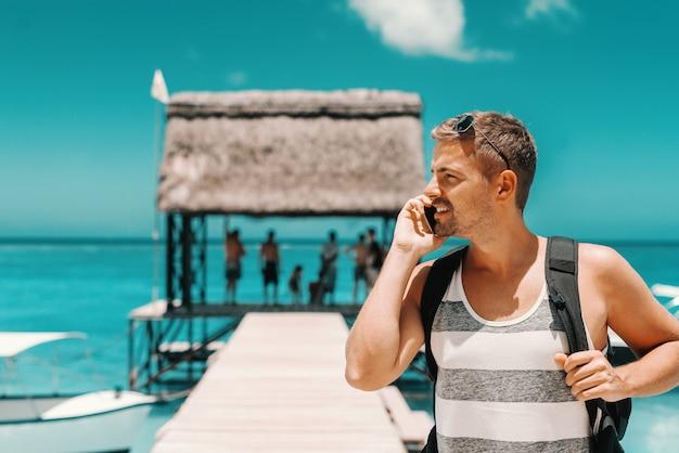 Retrato de hombre guapo caucásico con teléfono inteligente mientras está de pie en el muelle y mirando a otro lado. concepto de vacaciones de verano. Foto Premium