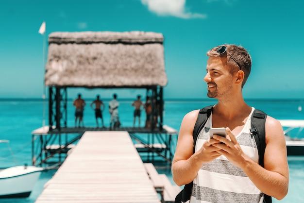 Retrato de hombre guapo caucásico con teléfono inteligente mientras está de pie en el muelle y mirando a otro lado. en el océano de fondo. concepto de vacaciones de verano. Foto Premium