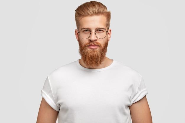 Retrato de hombre guapo elegante con peinado de moda, se ve en serio Foto gratis