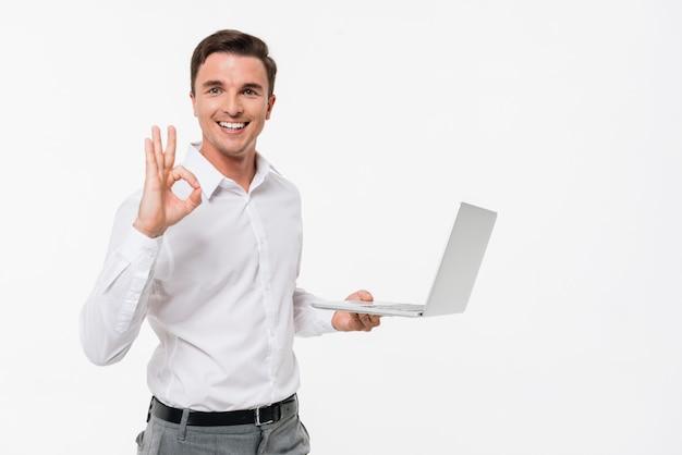 Retrato de un hombre guapo sonriente con laptop Foto gratis
