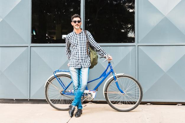 Retrato de hombre inclinado cerca de su bicicleta azul con su mochila Foto gratis