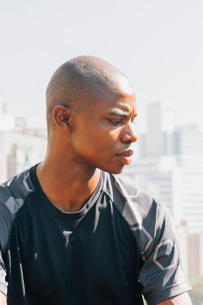 Retrato de un hombre joven afeitado africano mirando por encima del hombro Foto gratis