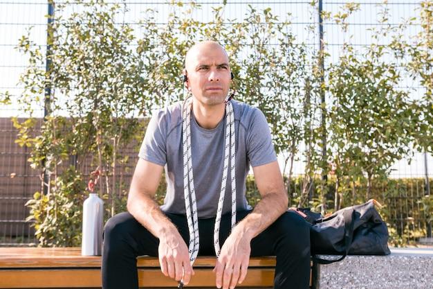 Retrato de un hombre joven de la aptitud que se sienta en banco con la cuerda alrededor de su cuello que mira lejos Foto gratis
