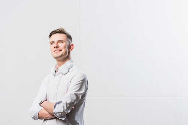 Retrato de hombre joven confiado con auriculares alrededor de su cuello de pie con los brazos cruzados contra la pared blanca Foto gratis