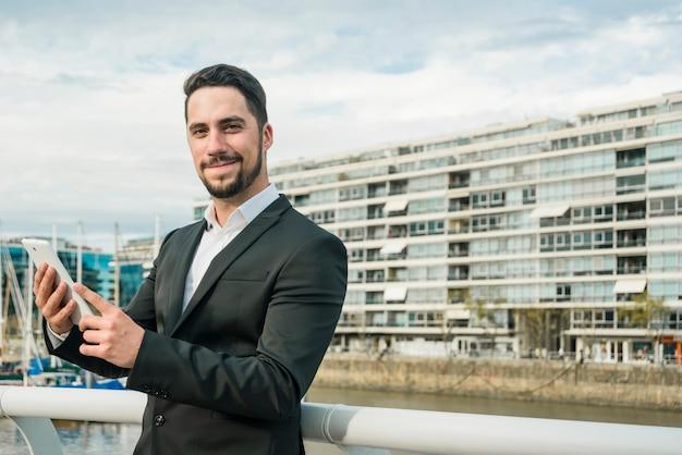 Retrato de un hombre joven confiado que sostiene el teléfono móvil en la mano que mira la cámara Foto gratis