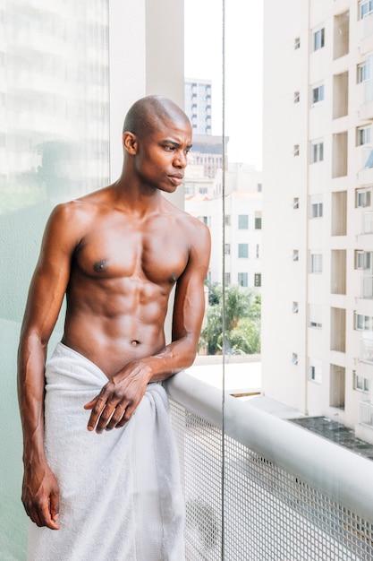 Retrato de un hombre joven descamisado afro que se coloca en el balcón que mira hacia fuera Foto gratis