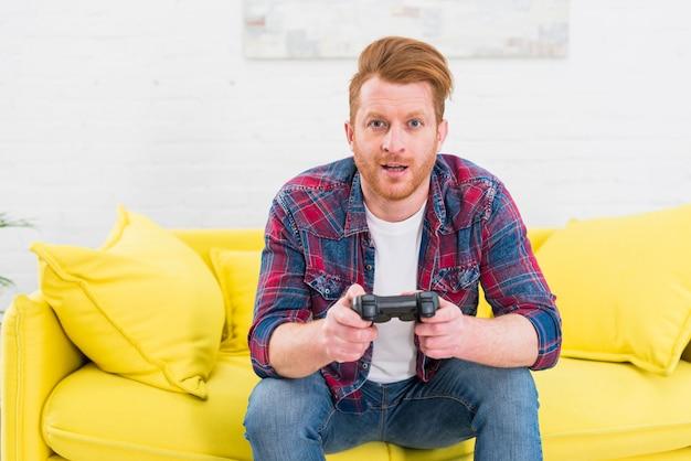 Retrato de un hombre joven emocionado que se sienta en el sofá amarillo que juega al videojuego Foto gratis