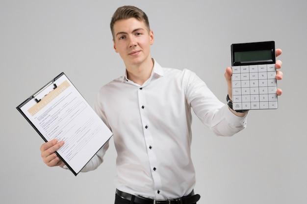 Retrato de hombre joven con forma de pago de facturas y calculadora en sus manos aisladas en blanco Foto Premium
