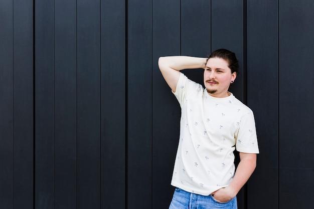 Retrato de un hombre joven con la mano en la cabeza y la mano en el bolsillo de pie contra la pared Foto gratis