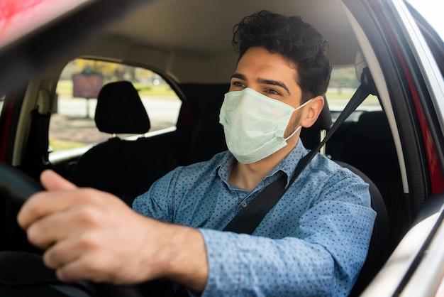 Retrato de hombre joven con mascarilla mientras conduce su coche camino al trabajo. concepto de transporte. nuevo concepto de estilo de vida normal. Foto gratis