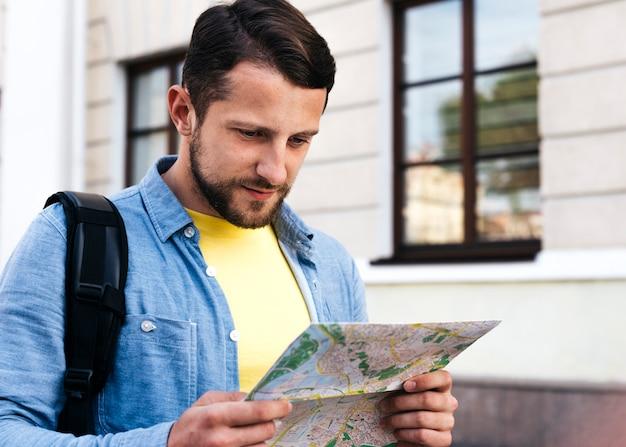 Retrato de hombre joven mirando el mapa durante el viaje Foto gratis
