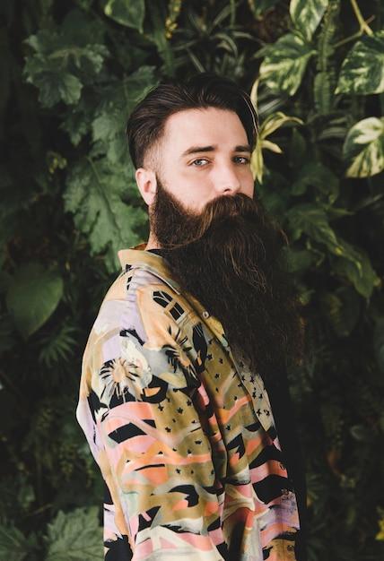 Retrato de un hombre joven que se coloca delante de las plantas que miran la cámara Foto gratis