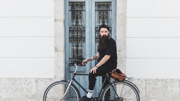 Retrato de un hombre joven que monta la bicicleta contra puerta cerrada Foto gratis