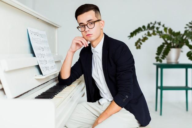 Retrato de un hombre joven sentado cerca del piano mirando a la cámara Foto gratis