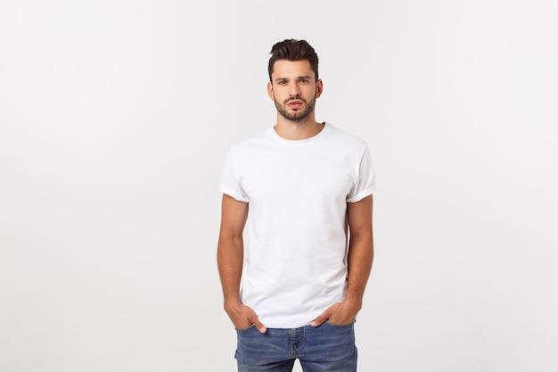 Retrato del hombre joven sonriente en una camiseta blanca aislada en blanco. Foto Premium