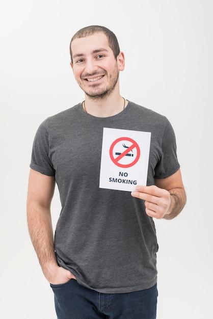 Retrato de un hombre joven sonriente con la mano en el bolsillo que muestra la señal de no fumar Foto gratis