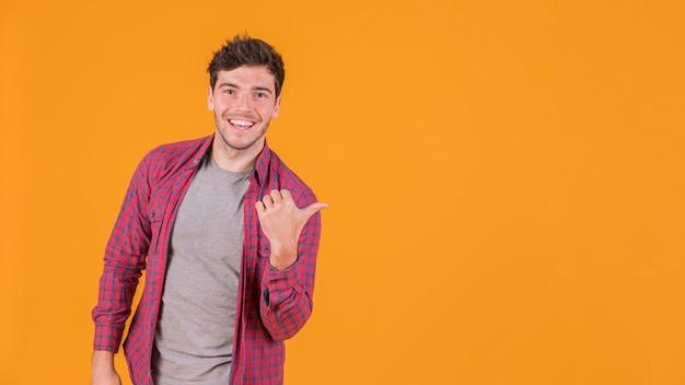 Retrato de un hombre joven sonriente que muestra el pulgar hacia arriba signo contra un telón de fondo naranja Foto gratis