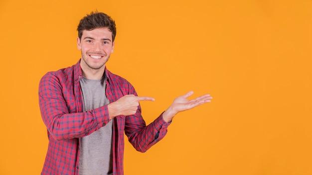 Retrato de un hombre joven sonriente que señala en algo contra el contexto coloreado Foto gratis