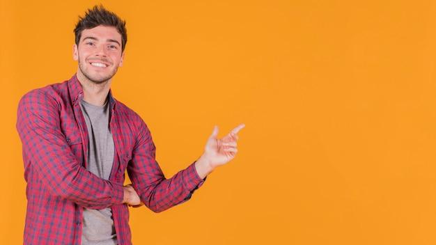 Retrato de un hombre joven sonriente que señala su dedo en algo contra el contexto anaranjado Foto Premium