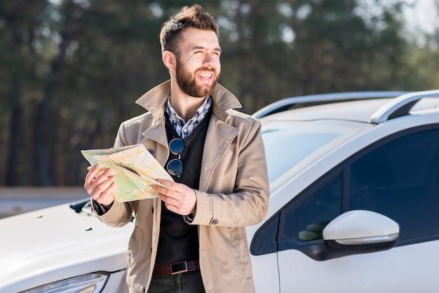 Retrato de un hombre joven sonriente que sostiene el mapa en la mano que se coloca cerca del coche que mira lejos Foto gratis