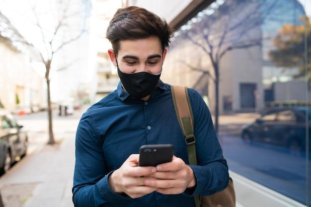 Retrato de hombre joven con su teléfono móvil mientras camina al aire libre en la calle. nuevo concepto de estilo de vida normal. concepto urbano. Foto gratis