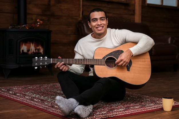 Retrato de hombre joven tocando la guitarra Foto gratis