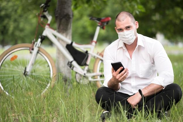 Retrato de hombre con máscara médica al aire libre Foto gratis