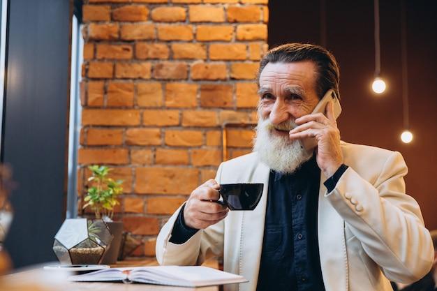 Retrato de un hombre mayor barbudo tomando café y usando el teléfono inteligente en la cafetería. retrato del hombre barbudo gris feliz que se sienta en café. Foto Premium
