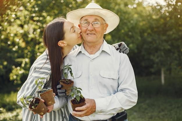 Retrato de hombre mayor con un sombrero de jardinería con granddaugher Foto gratis