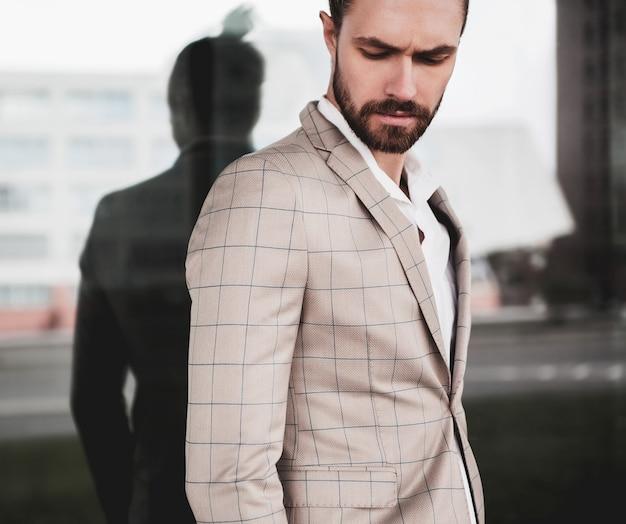 Retrato de hombre de modelo masculino de moda guapo sexy vestido con elegante traje a cuadros beige posando en el fondo de la calle Foto gratis