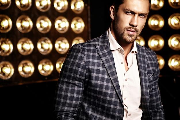 Retrato de hombre de modelo masculino de moda guapo sexy vestido con traje elegante sobre fondo negro de luces de estudio Foto gratis