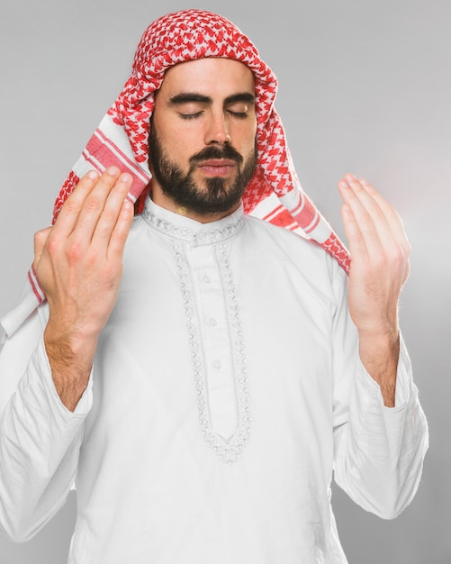 Retrato de hombre musulmán rezando con los ojos cerrados Foto gratis