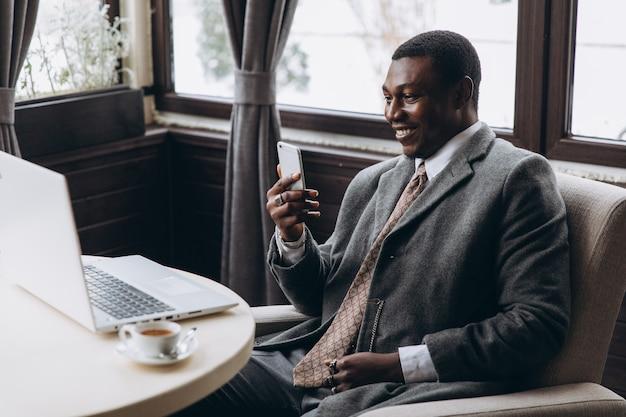 Retrato del hombre de negocios africano feliz que usa el teléfono mientras que trabaja en la computadora portátil en un restaurante. Foto Premium