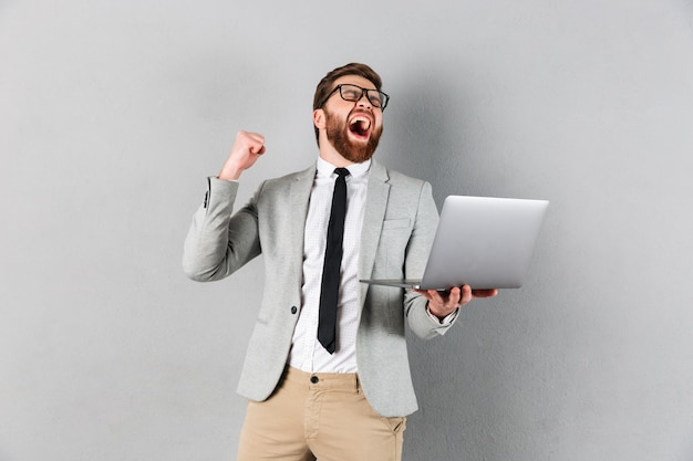 Retrato de un hombre de negocios alegre vestido con traje Foto gratis