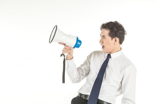 El retrato del hombre de negocios asiático joven elegante que lleva la camisa blanca grita con el megáfono del altavoz inalámbrico en fondo blanco aislado y copia el espacio. Foto Premium