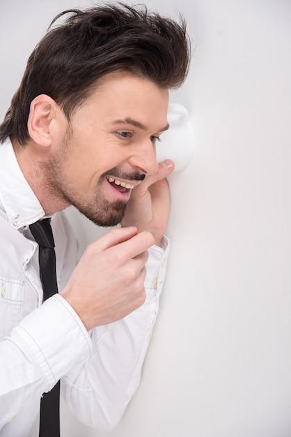 Retrato del hombre de negocios joven que usa un vidrio como teléfono. Foto Premium