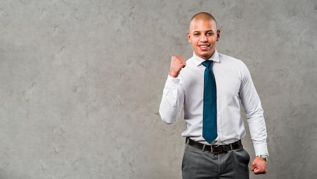 Retrato de un hombre de negocios joven sonriente que se opone a la pared gris que aprieta su puño Foto gratis