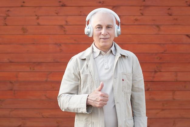 Retrato de un hombre de negocios maduro mostrando el pulgar hacia arriba sobre fondo de pared de madera Foto Premium