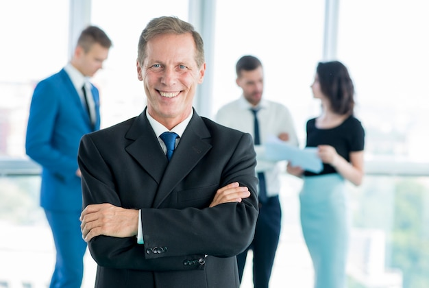 Retrato de un hombre de negocios maduro sonriente con los brazos cruzados Foto gratis