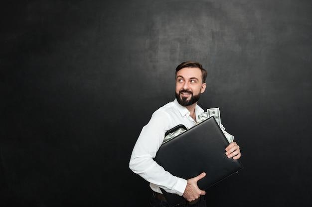 Retrato de hombre de negocios rico feliz llevando maletín lleno de billetes de un dólar y mirando hacia atrás, aislado sobre gris oscuro Foto gratis