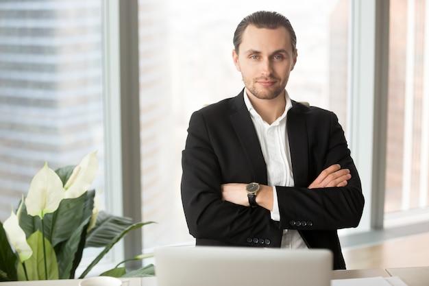 Retrato del hombre de negocios sonriente hermoso en oficina Foto gratis
