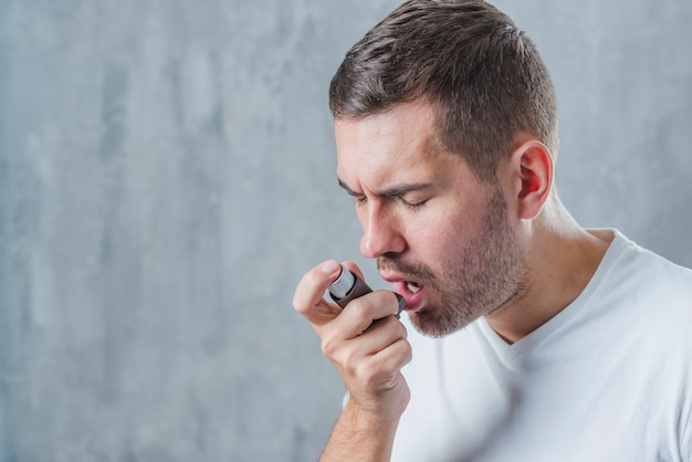 Retrato de un hombre con los ojos cerrados usando un inhalador para el asma Foto gratis